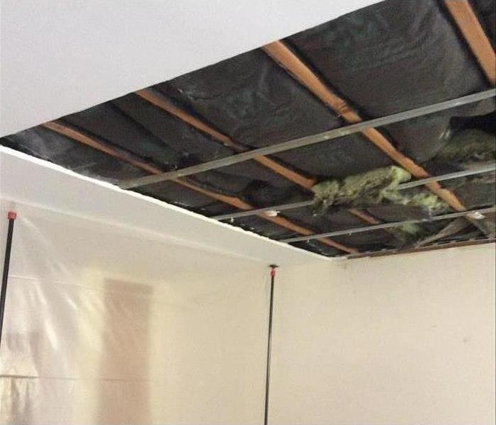 Ceiling material removed exposing wood and metal framing