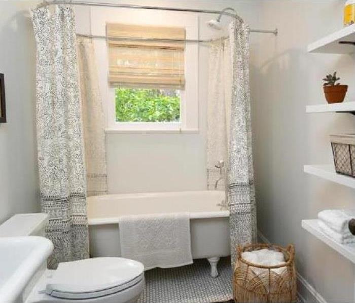 White bathroom with a tub and toilet