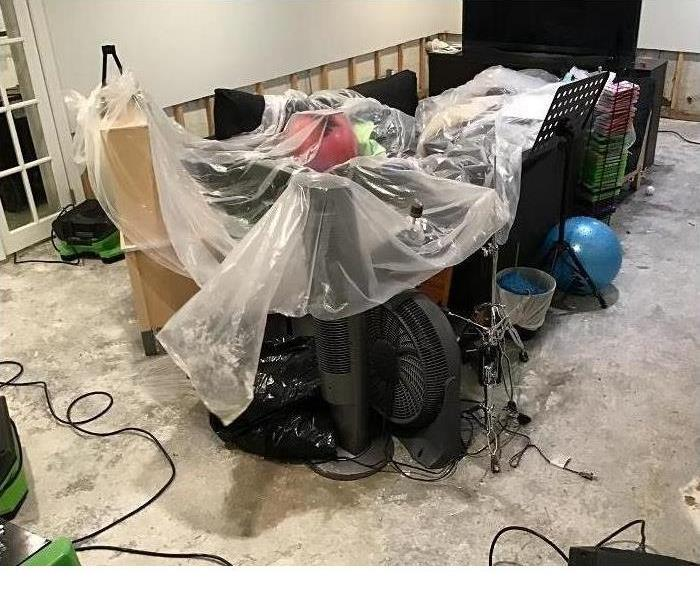 Customer's belongings in a basement under protective, plastic covering