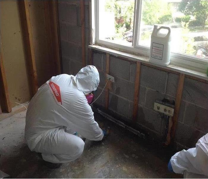 Crew member in PPE cleaning a wall